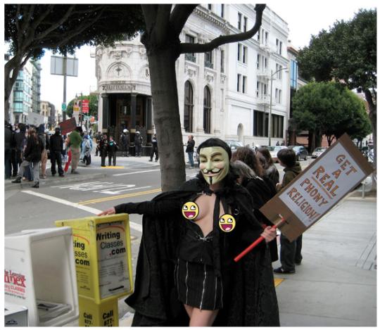 «Raidfag Wench» de Anonymous manifestándose contra la Iglesia de la Cienciología, 2008. (en el cartel: «Conseguid una verdadera religión falsa»)